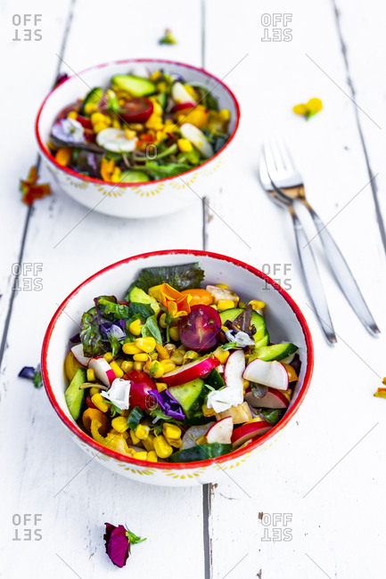 Bowls of mixed salad with edible flowers