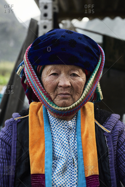 Ha Giang, Vietnam - February 15, 2018: Headshot of authentic Hmong ethnic elderly woman looking at camera wearing colorful costume.