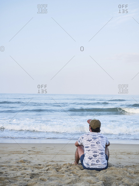 Young adult alone at the beach sitting on sand watching sunset pensive
