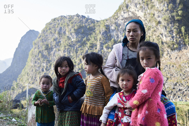 Ha Giang, Vietnam - February 16, 2018: Family photo of mother looking away surrounded by her children against rocky landscape.