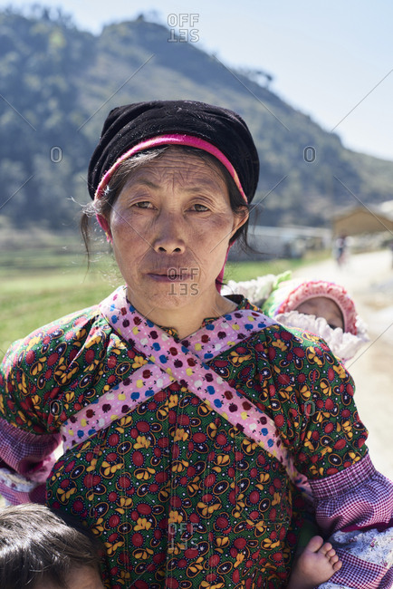 Ha Giang, Vietnam - February 16, 2018: Portrait of a senior woman looking at camera carrying baby on her back. Authentic Hmong ethnic group.