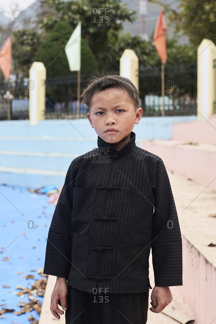 Ha Giang, Vietnam - February 17, 2018: Portrait of Hmong hill tribe little boy with serious face expression looking at camera wearing black costume.