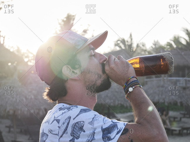Milennial brunette man drinking a bottle of beer at the beach against sunset and sunlight.