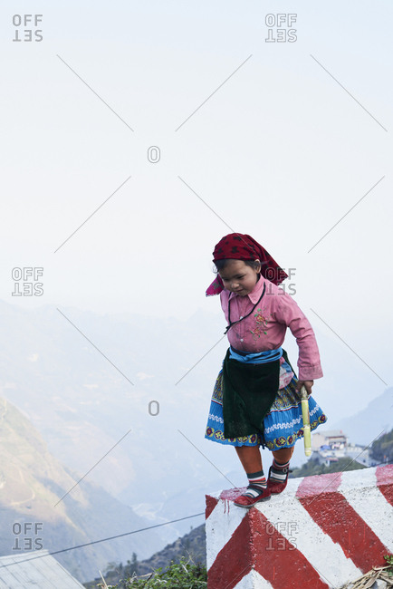 Ha Giang, Vietnam - February 16, 2018: Indigenous little girl wearing traditional Hmong ethnic costume walking on a fence of a cliff.