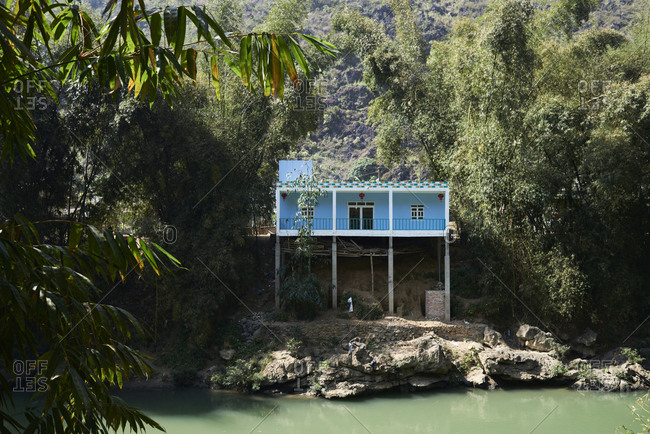 Beautiful blue house in idyllic location on the top of a river surrounded by nature in small mountain village.
