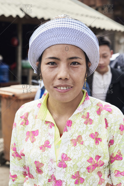 Ha Giang, Vietnam - February 17, 2018: Authentic Hmong indigenous young woman portrait wearing white traditional hat and looking at camera.