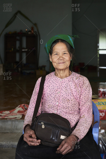 Ha Giang, Vietnam - February 17, 2018: Portrait of elderly Hmong indigenous woman sitting outside her house selling goods in small village.