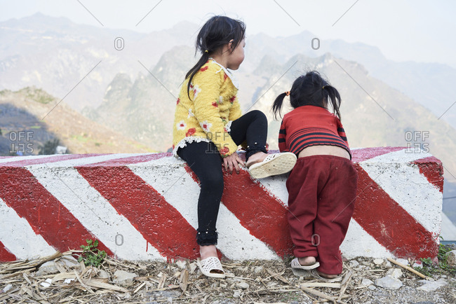 Ha Giang, Vietnam - February 16, 2018: Cute indigenous little girls watching over rocky landscape sitting on a red traffic fence.