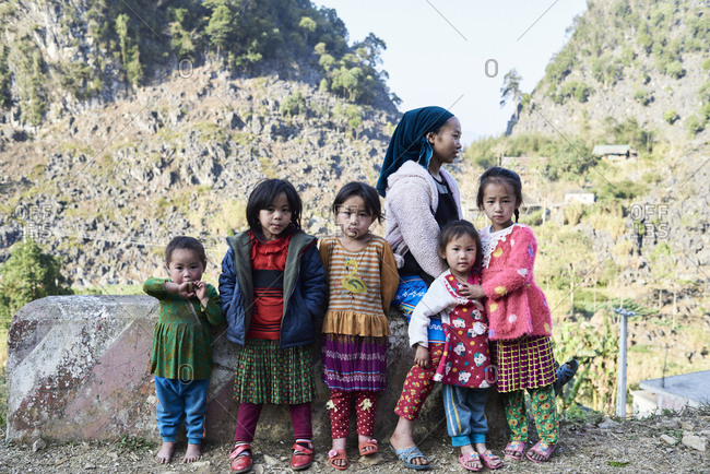 Ha Giang, Vietnam - February 16, 2018: Family photo of mother looking away surrounded by her children looking at camera. Wearing colorful outfit.