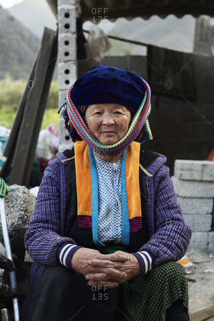Ha Giang, Vietnam - February 15, 2018: Portrait of authentic Hmong ethnic elderly woman sitting on the street looking at camera wearing traditional costume.
