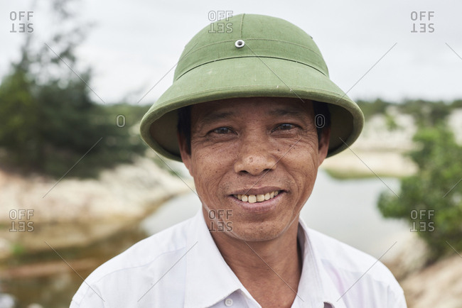 Dong Hoi, Vietnam - January 28,2018: Portrait of a Vietnamese rice field worker wearing green hat and smiling at camera.