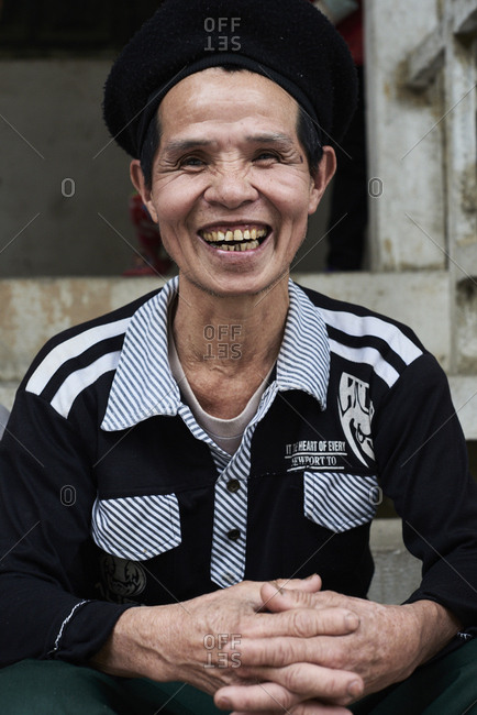 Ha Giang, Vietnam - February 18, 2018: Happy Hmong senior man laughing at camera wearing traditional black hat.