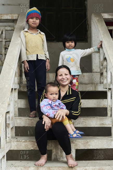 Ha Giang, Vietnam - February 18, 2018: Family portrait of a single mother with three kids sitting on a staircase barefoot and smiling at camera.