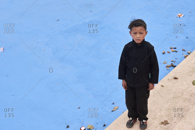 Ha Giang, Vietnam - February 17, 2018: Creative portrait of Hmong hill tribe little boy with serious face expression looking at camera wearing black costume.