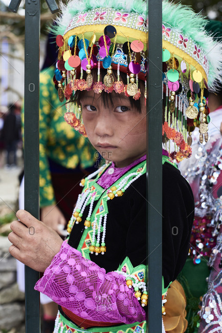 Ha Giang, Vietnam - February 17, 2018: Portrait of Hmong ethnic little girl with sad face expression looking at camera wearing colorful hat.