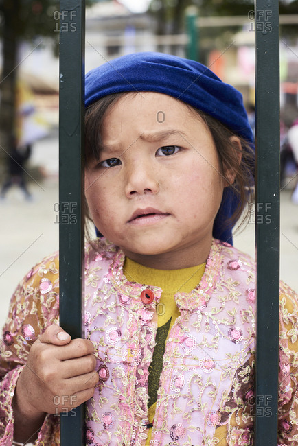 Ha Giang, Vietnam - February 17, 2018: Portrait of Hmong ethnic little girl with sad face expression looking at camera.