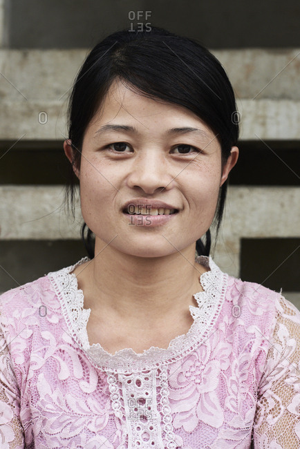 Ha Giang, Vietnam - February 18, 2018: Portrait of authentic northern vietnam young woman wearing pink costume and looking at camera.