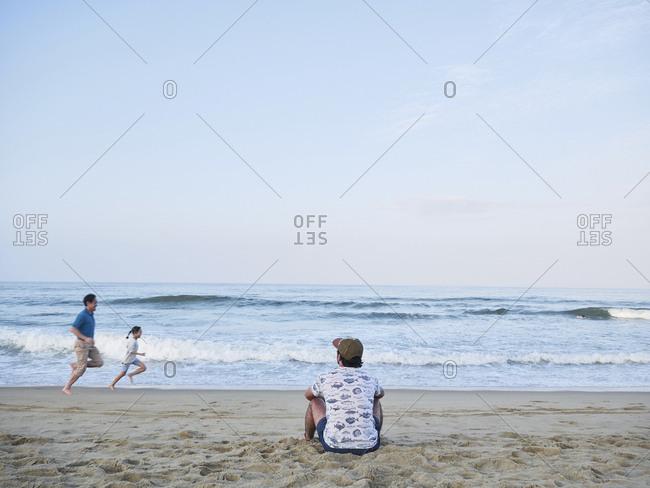 Hoi An, Vietnam - January 21, 2018: Faceless man watching sunset and family running across the seashore.