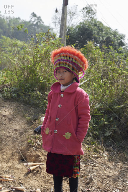 Ha Giang, Vietnam - February 15, 2018: Portrait of Hmong ethnic junior girl looking at camera wearing traditional costume.