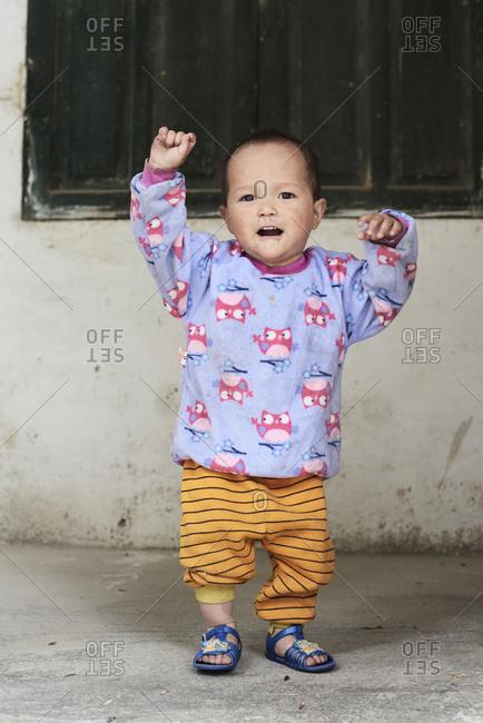 Ha Giang, Vietnam - February 18, 2018: Happy little boy dancing at home wearing pajamas looking at camera.