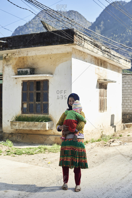Ha Giang, Vietnam - February 16, 2018: Portrait of authentic Hmong ethnic senior woman holding granddaughter on chest.