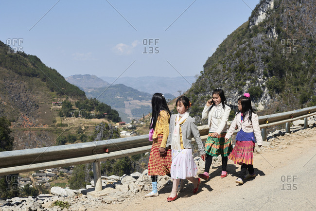 Ha Giang, Vietnam - February 16, 2018: Group of vietnamese girl friends walking together and chatting on the road of mountain village.