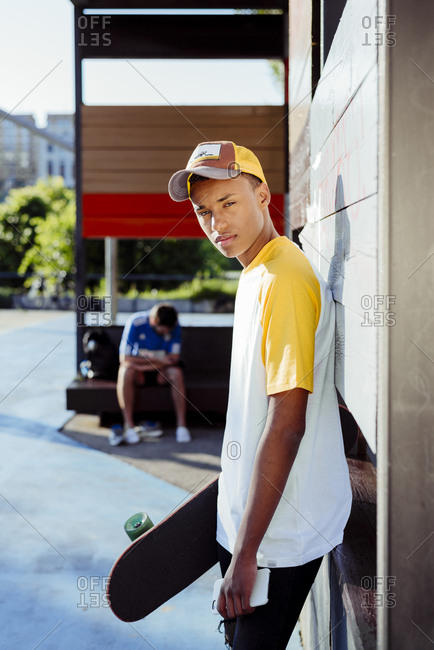 Young black man with baseball t-shirt and cap holding a skateboard posing in the park