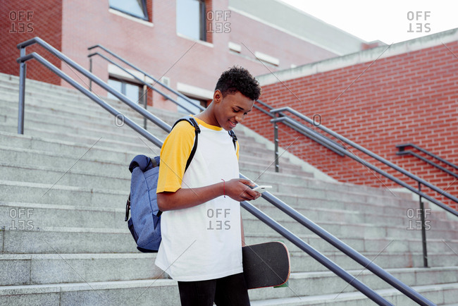 Young black student going down stairs using the phone and holding a skateboard