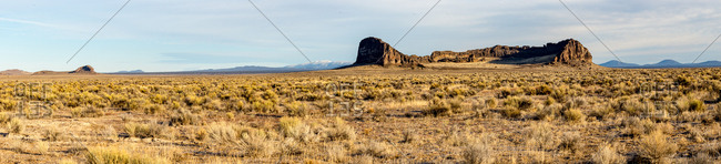 A panorama of sagebrush and rock formations in front of mountains, Oregon, United States of America, North America