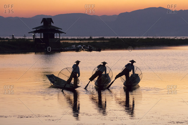 February 23, 2018: Three fishermen balance on one leg at sunset on Inle Lake, Shan State, Myanmar (Burma), Asia