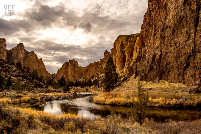 A river running through a valley with large rock formations on either side, Oregon, United States of America, North America