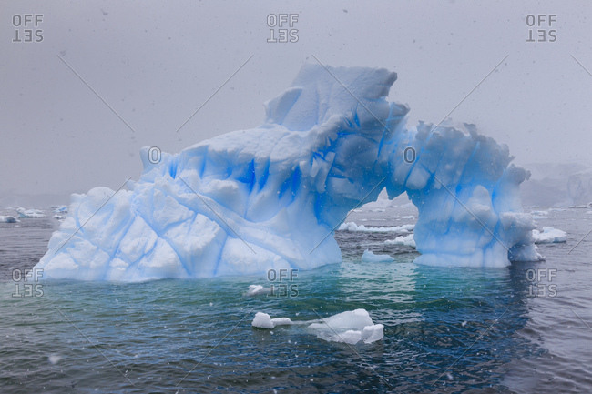 Blue iceberg arch in snowy weather, from sea level, Waterboat Point, Paradise Bay, Graham Land, Antarctic Peninsula, Antarctica, Polar Regions