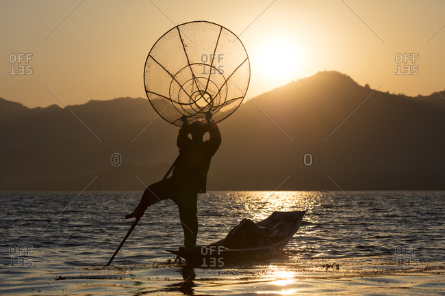 February 22, 2018: A fisherman standing on one leg and holding his fishing net at sunset on Inle Lake, Shan State, Myanmar (Burma), Asia