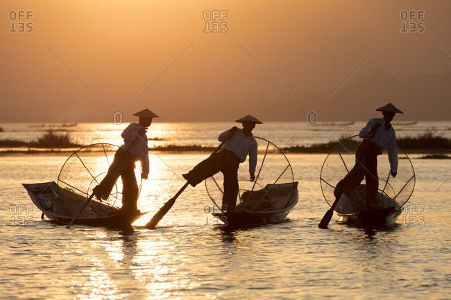 February 23, 2018: Three fishermen row with one leg at sunset on Inle Lake, Shan State, Myanmar (Burma), Asia