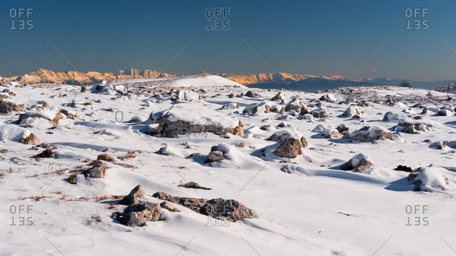Rocks emerge from the blanket of snow, in the background  the Julian Alps, Piancavallo, Friuli Venezia Giulia, Italy