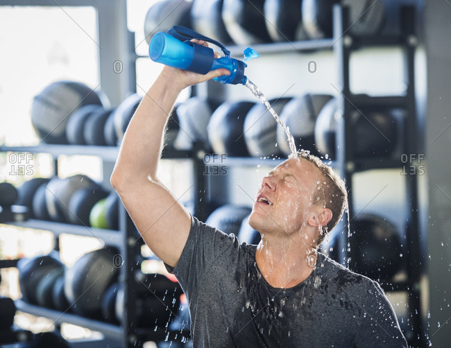 Man pouring water on himself in gym