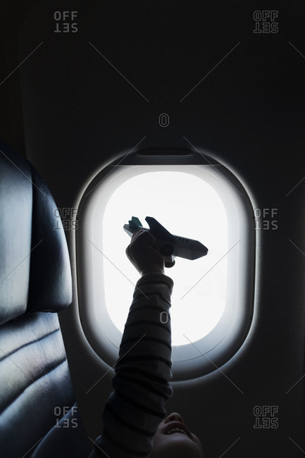 Silhouette of girl holding to airplane on airplane