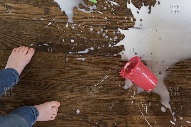 Boy's feet by spilt milkshake