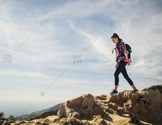 Woman hiking over rocks