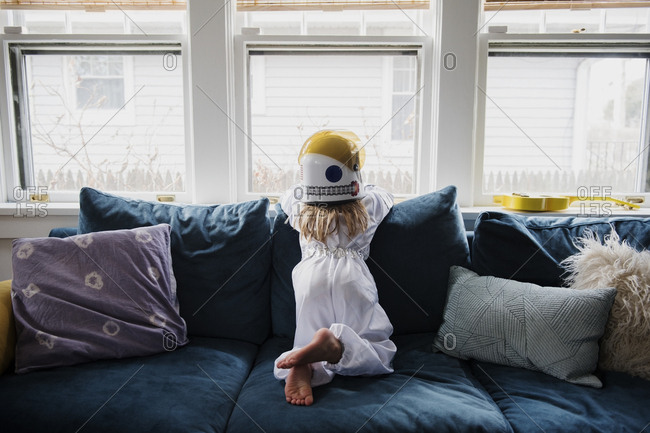 Girl wearing helmet on sofa by window