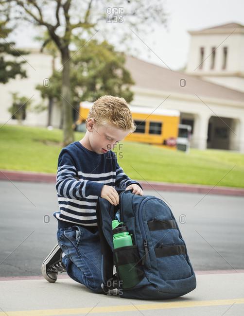 Boy kneeling by backpack