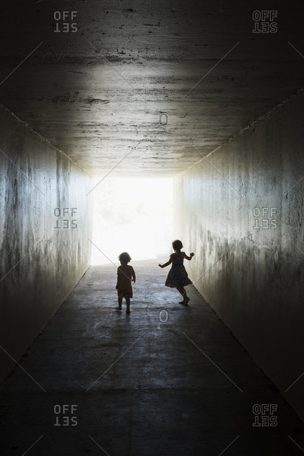 Silhouettes of children in tunnel