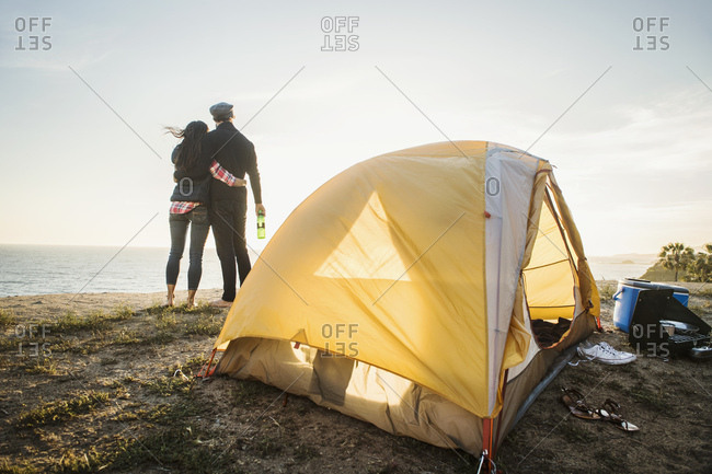 Couple by tent at beach