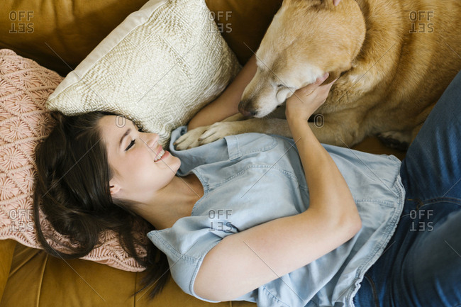 Woman lying on sofa with dog