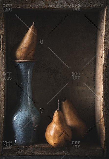 Still life with pears on vintage vase in wooden box