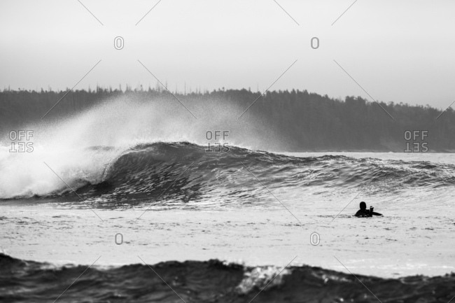 Surfer in water waiting for approaching large wave