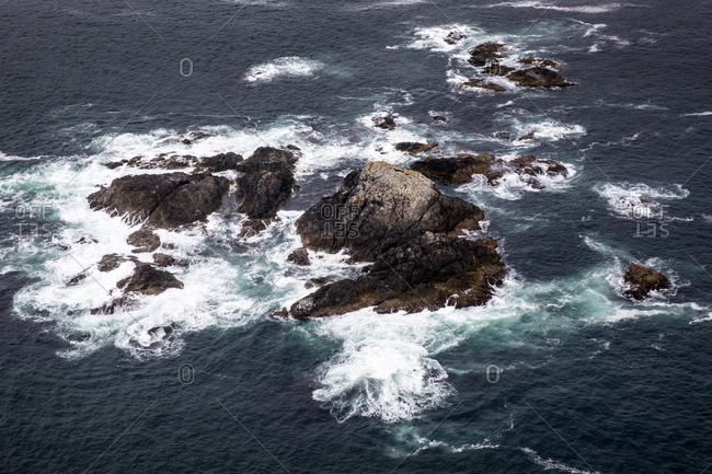 Aerial view of waves breaking on rocky islands