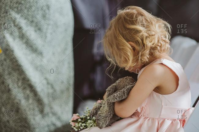 Little girl holding stuffed animal at wedding