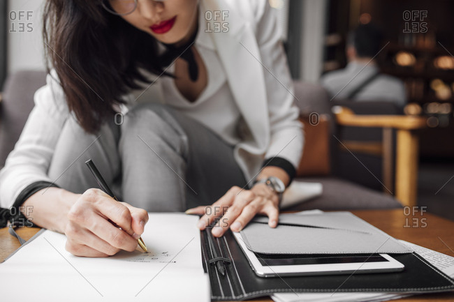 Cropped elegant businesswoman sitting at cafe and writing on paper