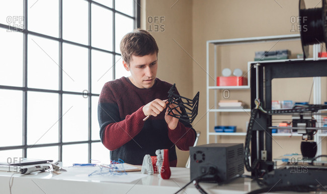 Young man graphic designer  processing object made on 3d printer